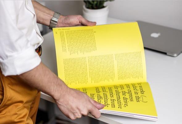 designer-flipping-through-yellow-magazine-img-D